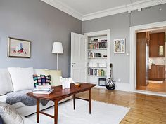 Grey walls warm floors and a book shelf inside an unused door frame