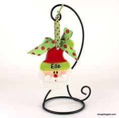 "Adorable Santa hand painted ceramic layered ornament.  Size: 6"" x 4"".  Personalization is available for an additional charge.  If you wish to have your ornament personalized please type  the name in the drop down menu below.  The name will be  personalized in black vinyl lettering.  Max characters (10).  Black ornament hanger not included.  Free personalization on this item!  In order to receive the free personalization you must click on the item line and enter the name in the NAME box.   …"
