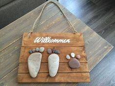"Was du brauchst: Holzbrett verschiede… What you'll need: wooden board different sized stones ""welcome"" lettering brush color craft glue chalk pen drawstring … Glue Crafts, Diy And Crafts, Crafts For Kids, Stone Crafts, Rock Crafts, Wooden Door Signs, Welcome Door Signs, Rock And Pebbles, Diy Gift Box"