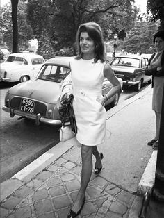Jackie O wears a white shift dress with heeled ballet flats and a mini white purse