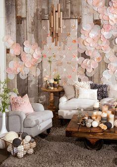 Uma ideia criativa para o lounge de sua festa ou casamento: pano de fundo composto de flores e tiras de papel coladas em um pedaço de papel kraft, ladeado porforminhas de cupcake sobrepostas, nas cores que combinem com o restante da decoração. Fofo e facinho de fazer!