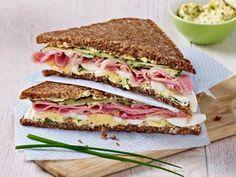 Gesundes Schinken-Sandwich für die Mittagspause im Büro. Zutaten: 1 kleines gekochtes Ei, 1/2 Teelöffel Halbfettmargarine, 1 Schnittlauch, ein wenig groben Senf, 4 bis 6 Scheiben Salatgurken, 2 Scheiben Brot, Kochschinken