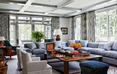 In the family room, a bespoke De Angelis sectional sofa in a Rose Tarlow Melrose House linen blend is grouped with antique English armchairs clad in a Jasper fabric and a cocktail table custom crafted from reclaimed oak; the curtains were made by Anthony Lawrence-Belfair using a Chelsea Editions linen.