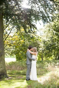 The bride and groom kiss under a sunlit tree at Brocket Hall.
