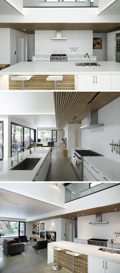 In this modern kitchen a long white island with wood accents has a built-in sink and plenty of storage. Above the stove, a slat wood accent feature in the ceiling with lighting continues into the living room.