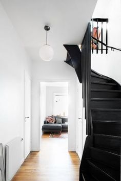 black staircase and white walls with globe pendant light fixture. Black Staircase, Open Staircase, Staircase Ideas, Black Banister, Staircase Walls, Entryway Stairs, Winding Staircase, Banisters, Interior Decorating