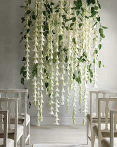 For a grand effect that's also budget-friendly, try this easy ceremony backdrop. Simply string crisp white Easter lilies on fishing line and hang them from dowels in staggered rows to put together an arrangement that brings to mind living wedding bells. Verdant grape ivy vines add a touch of wildness that transforms even the starkest venue into a dreamy retreat.