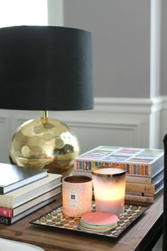 Black and gold lamp, stacked books, candles. I love it when it looks like people are living in a space. Details.