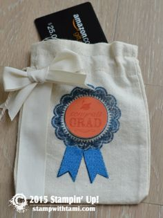 "Do you have a graduate on your gift giving list? Here's a fun graduation party ""gift bag"" from the Stampin' Up Muslin bags. A gift card holder stamped with the Retiring Blue Ribbon stamp set. The Tangerine Tango circle is cut from the 1-3/8″ Circle Punch."
