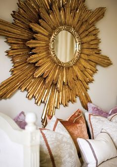 lovely sunburst mirrors above bead with decorative pillows