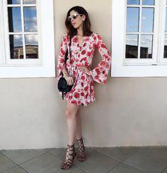 Vestido florido com estampa clara + sandália rasteira de tiras + bolsa pequena e preta.