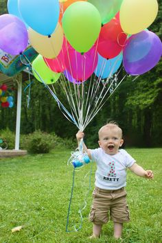 Cute first birthday photo with balloons.