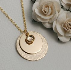 Elegant hammered gold necklace with stacked gold discs with crystal drop.