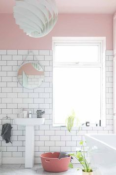 A pink and white bathroom is always a head stunner with white marble flooring, white subway tile, pink walls and a statement white pendant light. A round mirror over the porcelain white basin is a must. Image by nest.co.uk.
