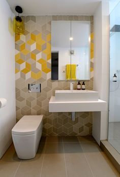 Fun geometrical wallpaper in this small modern bathroom