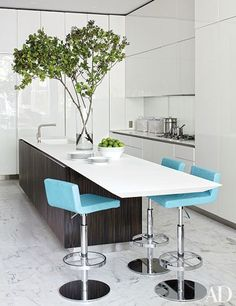 Derin's Fold barstools add a pop of color in the sleek white Boffi-clad kitchen of a Manhattan brownstone remodeled by Delphine Krakoff of Pamplemousse Design.