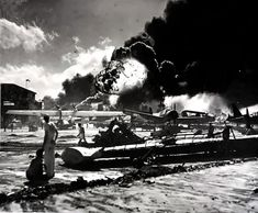 Japanese attack on Pearl Harbor. The wreckage-strewn Naval Air Station. An explosion is visible in the background, 07 December 1941