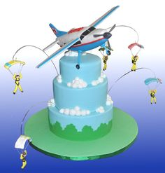An Airplane and skydiver cake for my Grandson's 5th birthday. Inspired from skydivers we watch from our backyard. Cessna is RCT with gumpaste skydivers and parachutes.Fondant covered cake with buttercream clouds.