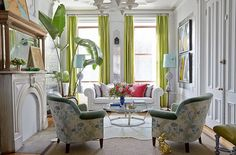 Chinoiserie patterned arm chairs add a sense of tradition to this modern living room filled with timeless white furnishings and pops of lime green and hot pink for a dose of contemporary color.