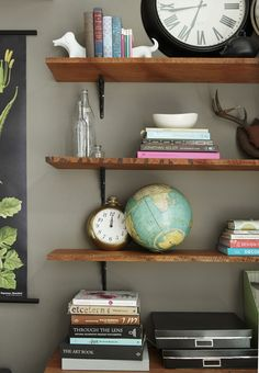 These are simple shelves that are unusual and would be easy to replicate as a DIY project.  Buy some black brackets and have Home Depot cut some higher quality wood for you.  Next stain the wood to your preferred shade and mount to wall.