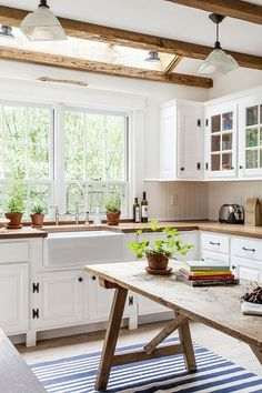 A stunning white and airy kitchen with beams in ceiling. Subway tiles, farmhouse sink, big bright window, this kitchen has it all! via Dream Book Design: