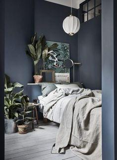 Dark walls, light floors, linen and lot of plants in the bedroom.