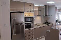 Cozinha cheia de armários e torre de eletrodomésticos