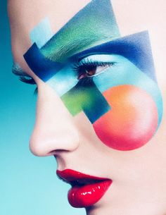 Blend of bold colours and shapes on the face against a pale face- abstract and innovative make-up- a different way of representing someone
