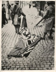 1944- Moroccan soldier drags a German flag through the street following the fall of Mulhouse, France, to the Allies.