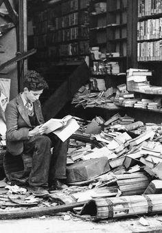 A boy reading in a bookstore ruined by an air raid. London, 1940