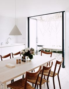 Bright white modern dining room with doors to patio.