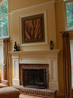 Brick fireplace with built-out drywall and trim that lines up over the windows