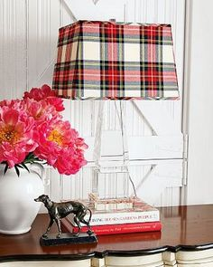 Look at this picture: Proof you can live with tartans year round. Love the lucite lamp base and the barn cross brace details behind it.