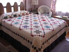 Pretty quilt - but I especially love the 'staging' --- the headboard, the light, the wicker chair <3