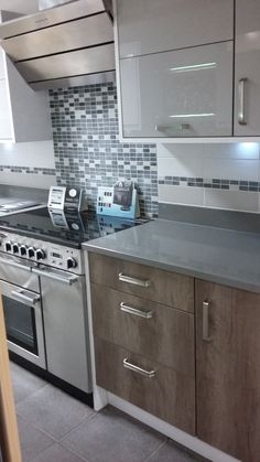 BY DESIGN Tiverton and Vienna Gloss Kitchen units, used together with mosaic tiles and Silestone TM Quartz Worktops at our Newton Abbot Showroom
