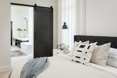 A+black+tufted+headboard+supports+a+bed+dressed+in+ivory+bedding+accented+with+ivory+pillows+and+a+black+and+white+pillow.