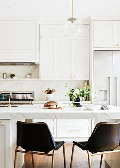 CB2 Roadhouse Black Leather Counter Stools pair together at a white marble top island featuring thick countertop detailed edge-lit by a glass and brass globe sconce.