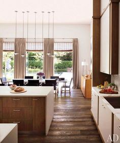 Modern Walnut Kitchen Island mixed with white cabinetry with walnut details.  Rustic Oak Flooring in open floorplan kitchen and dining.