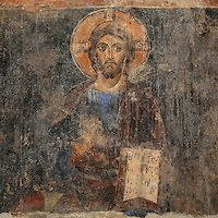 Fresco of Christ with crucifix halo and book, with hand raised in gesture of blessing, from the Church of Labova e Kryqit, or church of the Holy Cross, dedicated to St Mary, one of the oldest churches in Albania, mainly 13th century although with Byzantine foundations of 527-565 AD in the time of Emperor Justinian, Labova e Kryqit, Gjirokastra, Albania. The nave and aisle form a cruciform plan and the high central cupola is typically Byzantine. The interior walls are covered with 9 levels…