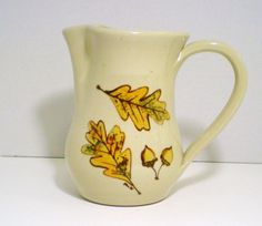 Kovack Pottery Seagrove NC Kovack pottery ceramic pitcher, sand colored hand turned and hand painted 6 inch pitcher with leaves and acorn. The pitcher has a 4 inch center diameter opening and is 5 1/2 inches across from spout to handle.