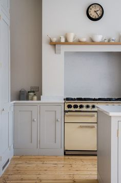 Shaker style oak cabinets painted in Farrow & Ball Pavilion Gray sit alongside a Falcon range cooker. An oak mantelpiece sits above with beautiful ceramics. The original pine flooring has been filleted, sanded, and lacquered.