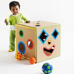 Put together this smart cardboard shape sorter to help your toddler learn shapes and sizes. What you'll need: 18x18x18-inch box, circle compass, ruler, pencil, cutting mat, X-Acto knife, adhesive contact paper, colored masking tape, hot-glue gun Make it: While box is flat, draw desired shapes on all six sides using a compass and/or ruler and pencil. Slide cutting mat behind shapes and cut out using an X-Acto knife. Trace each cutout circle onto contact paper, t...