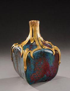 ** PIERRE ADRIEN DALPAYRAT (1844-1910) Vase à corps de forme cubique et col cylindrique en grès émaillé vert et rouge sang-de-boeuf, enserré dans une monture en bronze doré ciselé.