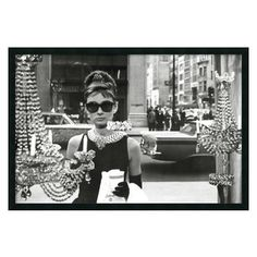 """Amanti Art - Audrey Hepburn, Breakfast at Tiffany's (Window) Framed with Gel Coated Finish - The image of Audrey Hepburn standing in front of the New York City jewelry store window from the movie Breakfast at Tiffany's has become so iconic, just about every shopping-obsessed woman has probably owned a version of it. If not, Holly Golightly might likely slap you upside the head with her """"Moon River"""" ukulele! Enjoy this great image as beautifully framed art on your wall. $79.95"""