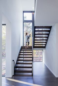 Dark wood stairs strongly contrast the white walls in this modern house and lead to the upper floor of the home. Windows span the height of the stairs and let in an abundance of natural light.