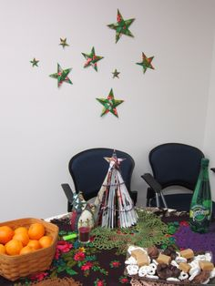 Setting up and decorating for office party:  5-point origami starts, folded magazine Christmas tree, and several crocheted doilies atop genuine Russian scarves.