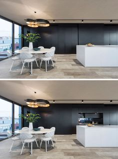 This black wall of cabinetry has a sliding panel that can cover part of the kitchen up when you don't want it on display. Open Plan Kitchen Dining, White Kitchen Island, Kitchen Layout, White Dining Table, Contemporary Kitchen Design, Living Room With Fireplace, Minimalist Kitchen, Black Walls, House Rooms
