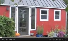 """VIDEO Tiny House Tour.  240 sq ft house """"ideal for 2 or 3"""" with ingenious bathroom. The large closet opens up and reveals the bathroom behind it. The extra space is put to good use as they have a full tub/shower unit. Their dual lofts offer privacy by being walled off, with stained glass windows looking onto the living space below. Projector and pull down movie screen allows for a 72"""" tv surface that easily disappears when not in use."""