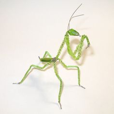 This sweet little Bug would love to winter in an indoor potted plant or in your window, maybe even hang out in a terrarium. Hes beaded on solid German wire covered with a variety of green beads. He stands only 5 inches high (antenna to toes) X 2 3/4 inches long X 2 inches wide.