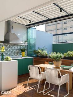 """A cobertura de ferro e vidro (Metalbox) protege a churrasqueira. Esta tela solar (A Morada), que pode ser recolhida, ameniza o excesso de claridade."""